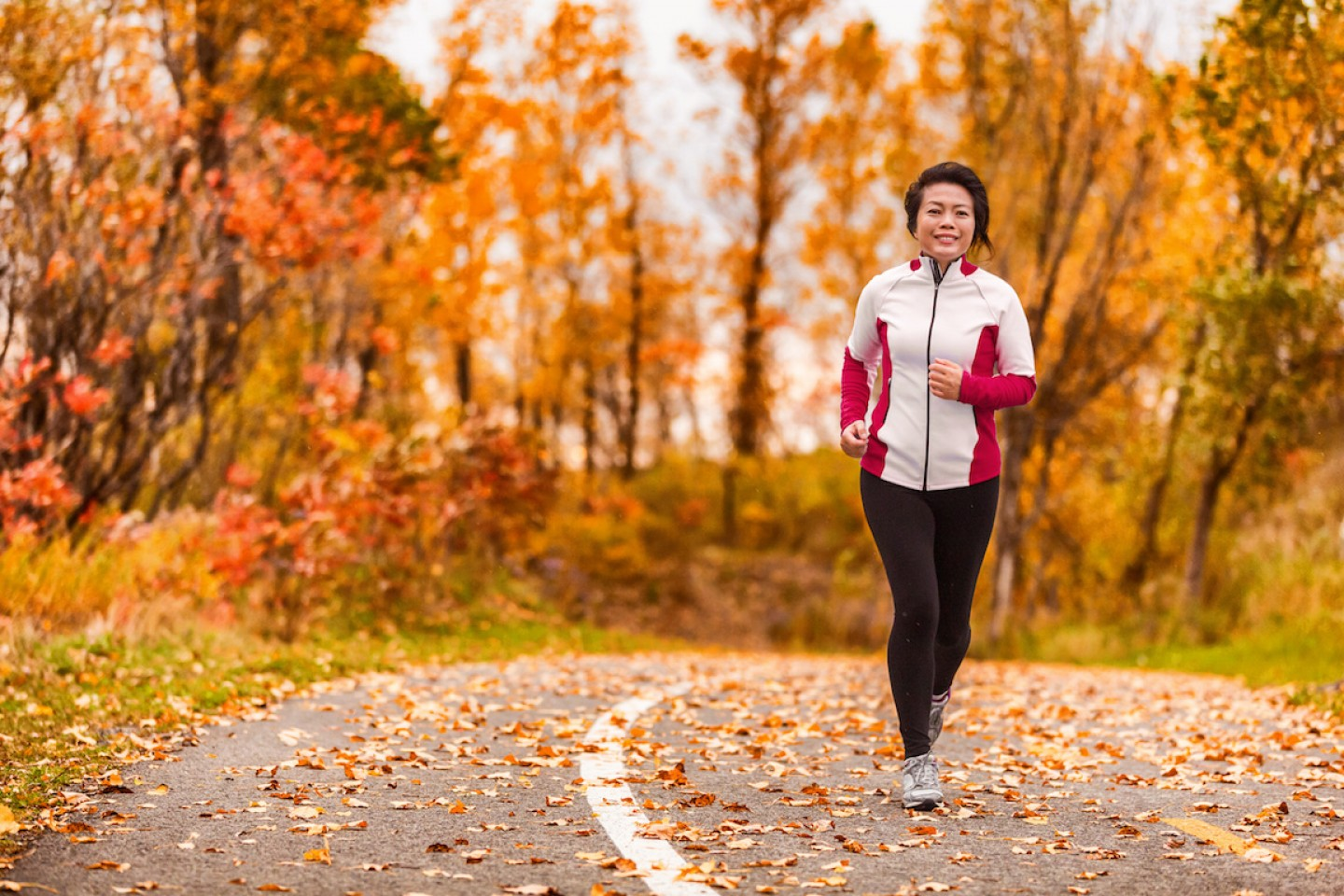 Middle age mature active and healthy Asian woman exercising weight loss body workout jogging running in park path autumn forest. Middle aged lifestyle. Lady in her 50s.